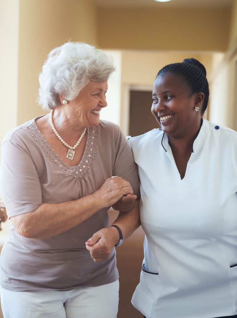 Smiling care worker and client walking at home