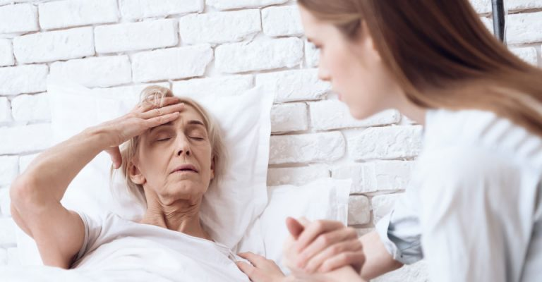 daughter holds elderly mothers hand who requires overnight care