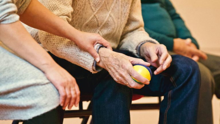 Elderly man holds ball whilst family members hold his hand
