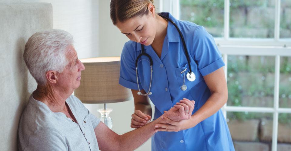 Hazelcare support worker examining senior man while providing emergency care